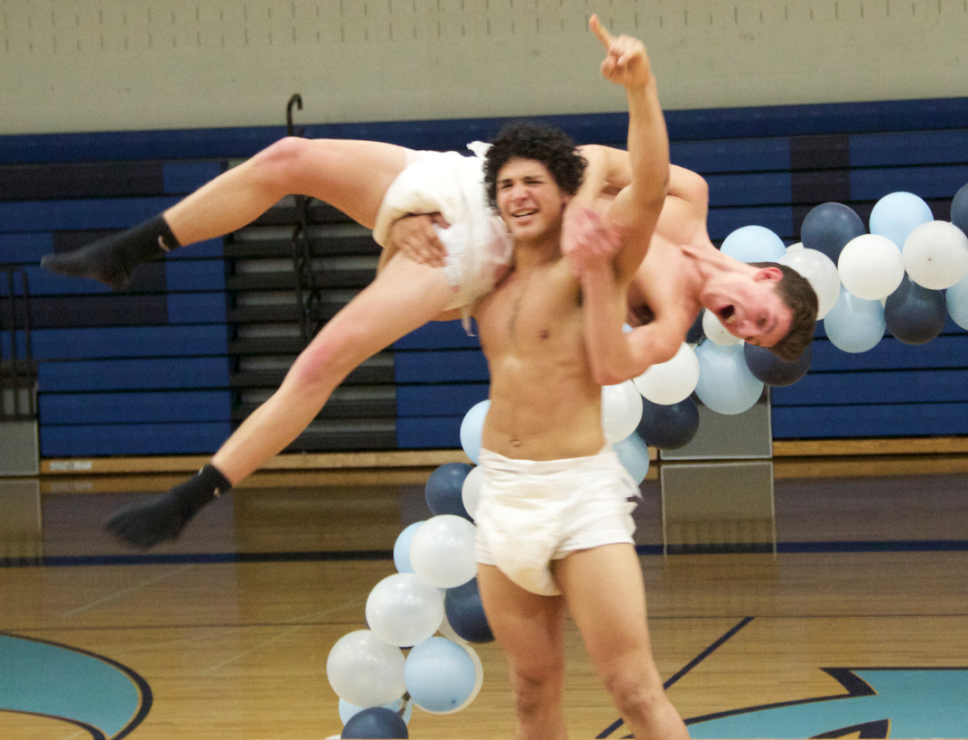 Martin Brazier lifts up his opponent, Parker Cowan after a sumo-wrestling match in adult diapers.